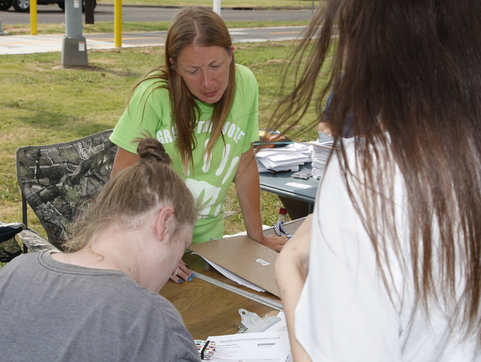 Photo - Tammy Searcy, center, of Green the Vote, registers people to vote and handles the signing of two marijuana petitions, for recreational marijuana and a constitutional amendment for medical marijuana, in Oklahoma City, Monday, July 30, 2018. Green the Vote, a group working to legalize recreational marijuana in Oklahoma, says it's gathered enough signatures to qualify for the ballot. (AP Photo/Sue Ogrocki)