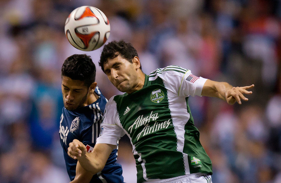 Photo - Vancouver Whitecaps' Matias Laba, of Argentina, and Portland Timbers' Diego Valeri, right, of Argentina, vie for the ball during the first half of an MLS soccer game in Vancouver, British Columbia, on Saturday, Aug. 30, 2014. (AP Photo/The Canadian Press, Darryl Dyck)