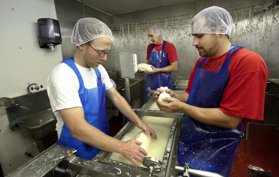 Photo - Shawn Duffy, left, Sam Lovera, and Kyle Arpoika make fresh cheese for Lovera's Italian Market in Krebs.  Jim Beckel - THE OKLAHOMAN