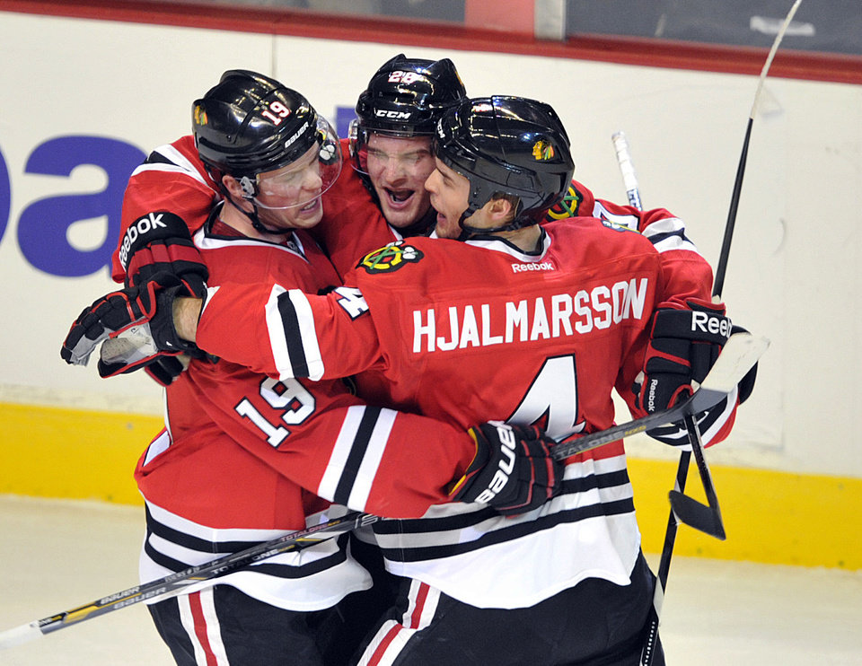 Chicago Blackhawks' Brandon Saad, center, celebrates with teammates Jonathan Toews (19) and Niklas Hjalmarsson (4) after Saad's goal against the Nashville Predators during the first period of an NHL hockey game Monday, April 1, 2013, in Chicago. (AP Photo/Jim Prisching)