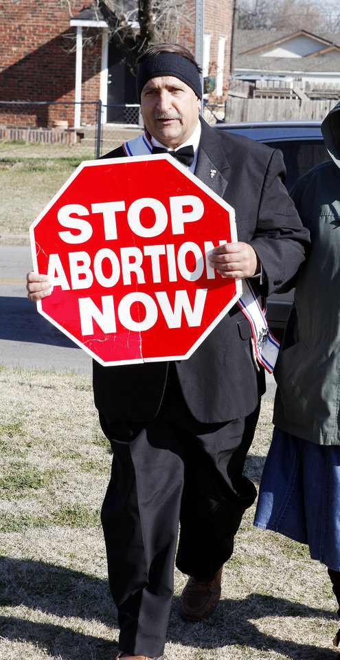 Richard Muller of Marlow carries a sign as he walks down Western Avenue. on Monday while participating in the 2013 March for Life OKC from Our Lady's Cathedral, 3214 N Lake Ave., to the state Capitol building.  <strong>PAUL B. SOUTHERLAND - PAUL B. SOUTHERLAND</strong>