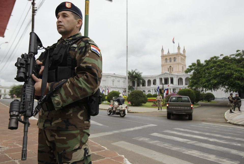 Photo -   Soldiers stand guard outside the Presidential Palace, in Asuncion, Paraguay, Friday, June 22, 2012. Paraguayan lawmakers voted Thursday to impeach President Fernando Lugo for his role in a deadly clash involving landless farmers and police. Lugo's impeachment trial was to begin Friday in Paraguay's Senate. (AP Photo/Jorge Saenz)