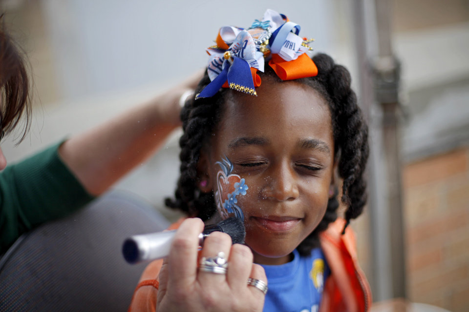 Photo - Kiayah Roane, 5, gets her face painted outside Chesapeake energy Arena before Game 4 of the Western Conference Finals in the NBA playoffs between the Oklahoma City Thunder and the San Antonio Spurs at Chesapeake Energy Arena in Oklahoma City, Tuesday, May 27, 2014. Photo by Bryan Terry, The Oklahoman