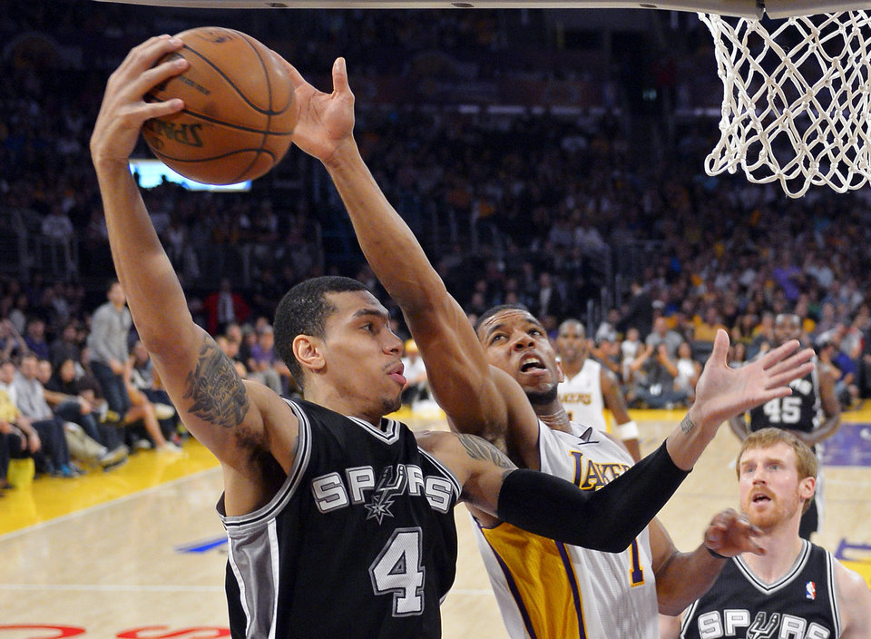 Photo - San Antonio Spurs guard Danny Green (4) grabs a rebound away from Los Angeles Lakers guard Darius Morris during the first half in Game 4 of a first-round NBA basketball playoff series, Sunday, April 28, 2013, in Los Angeles. (AP Photo/Mark J. Terrill)
