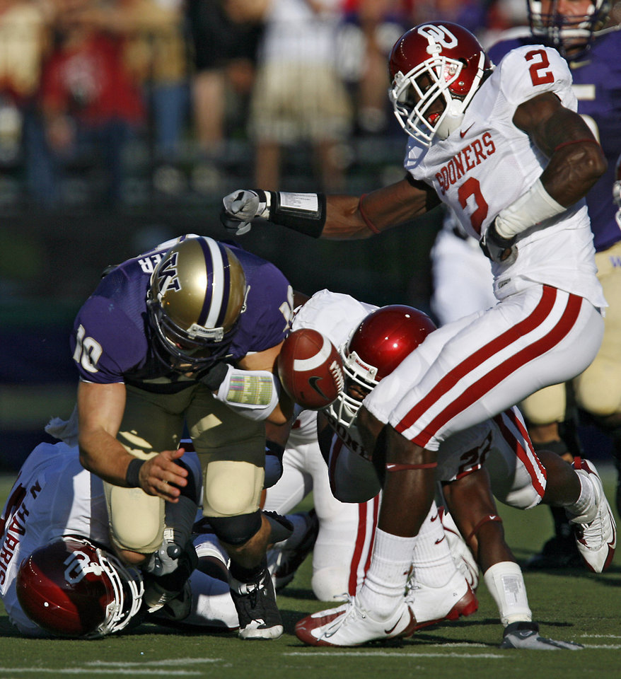 Photo - Oklahoma's Brian Jackson (2) strips the ball from Washington quarterback Jake Locker (10) to cause a fumble during the first half of the college football game between the University of Oklahoma Sooners (OU) and the University of Washington Huskies (UW) at Husky Stadium on Saturday, Sep. 13, 2008, in Seattle, Wash. 