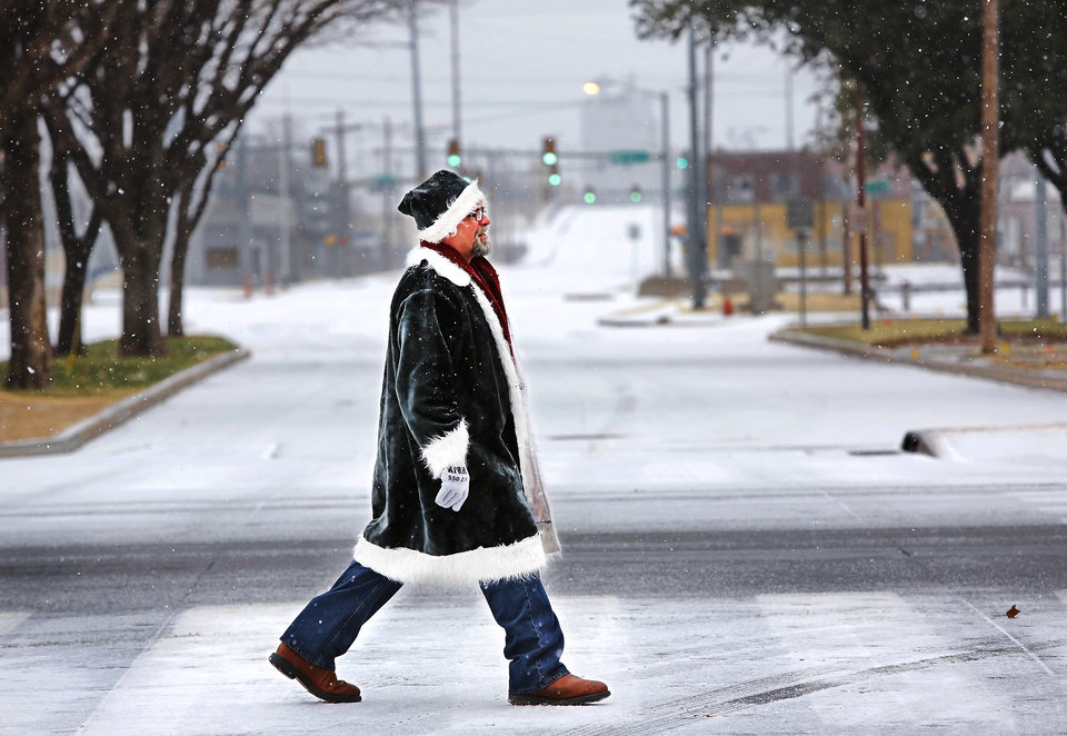 Bill Long, a local arborist, walks across S. Robinson as he leaves the Cox Convention Center after volunteering at the Red Andrews Dinner. Long said he enjoyed the morning snowfall and to celebrate the white Christmas, he dressed in a Santa suit with red and green bows attached to his coat. A white Christmas in downtown Oklahoma City, Dec. 25, 2012. Looking west down NW 4th from Harvey. Photo by Jim Beckel, The Oklahoman