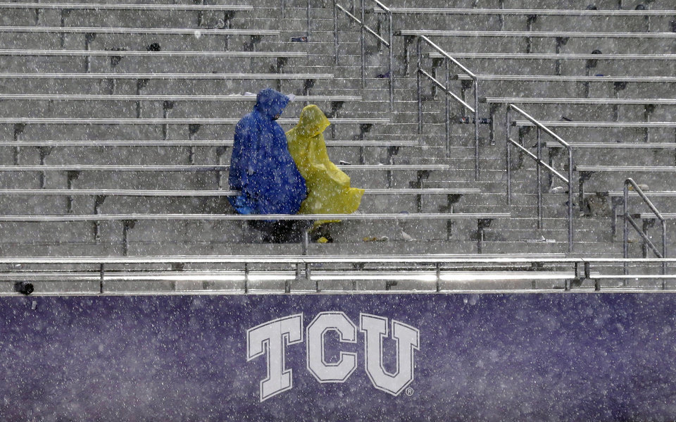Photo - Fans sit in the stands during a thunder delay in the second quarter of an NCAA college football game between Texas and TCU, Saturday, Oct. 26, 2013, in Fort Worth, Texas. (AP Photo/LM Otero)