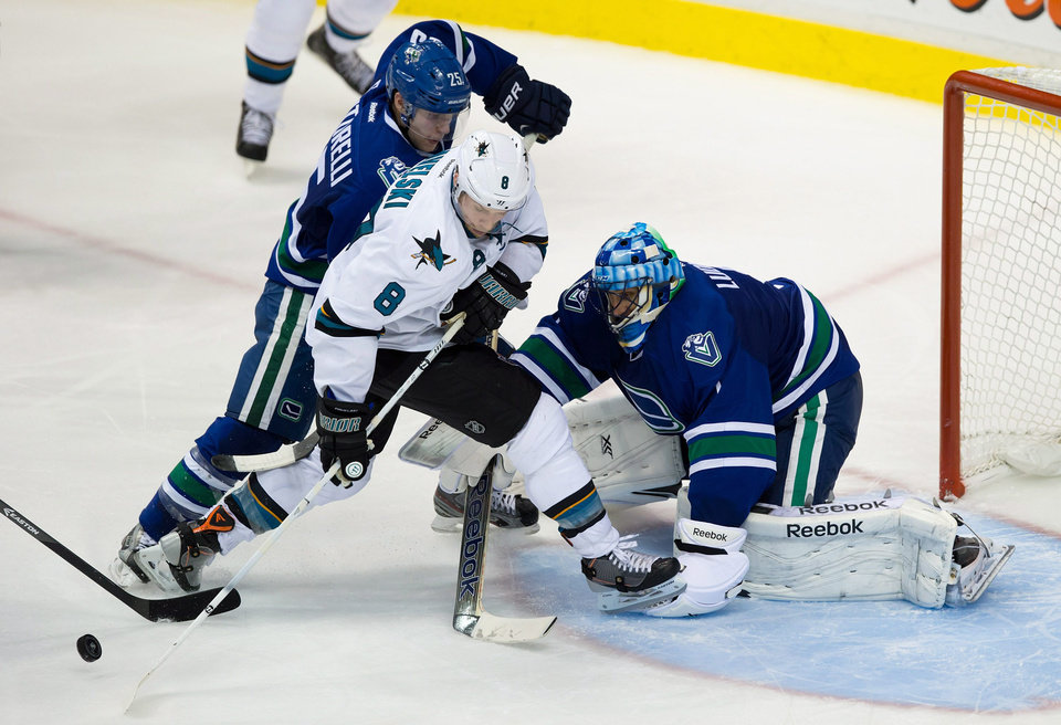 Vancouver Canucks' Mike Santorelli, left, checks San Jose Sharks' Joe Pavelski, center, as he attempts a shot on Canuck goalie Roberto Luongo during third period NHL hockey action in Vancouver, British Columbia, on Thursday Nov. 14, 2013. (AP Photo/The Canadian Press, Darryl Dyck)