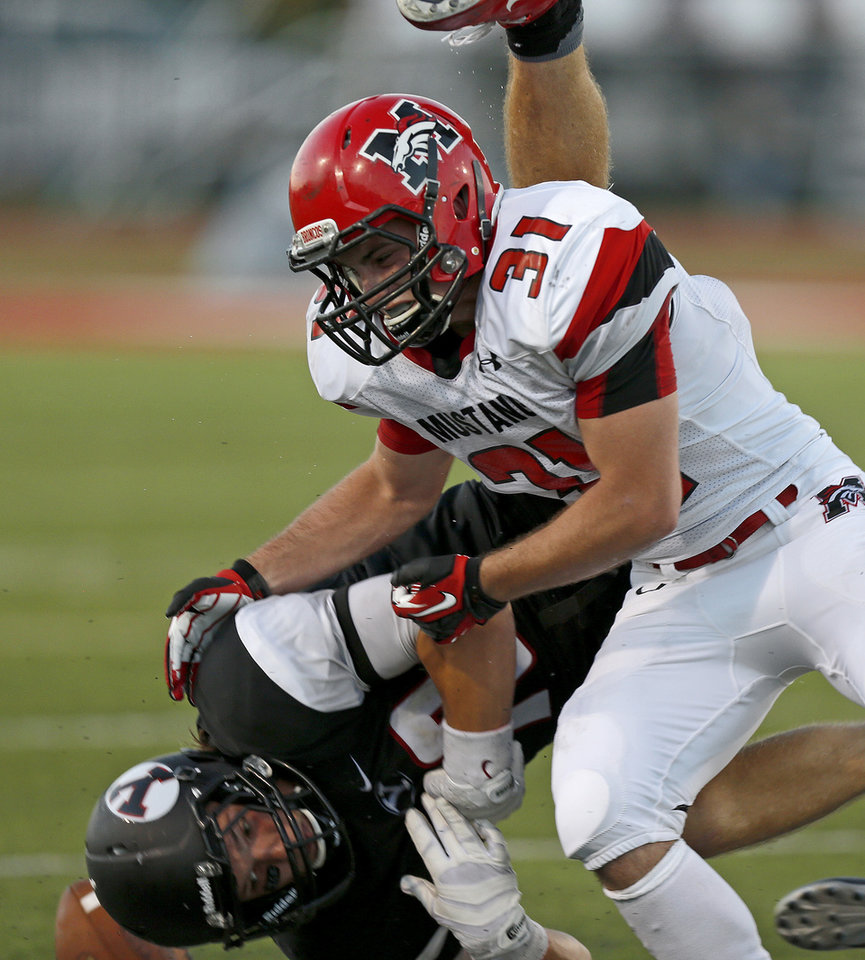 Mustang's Jace Eplin hits Yukon's Brandon Andraszek during a high school football game in Yukon, Okla., Friday, August 31, 2012. Photo by Bryan Terry, The Oklahoman