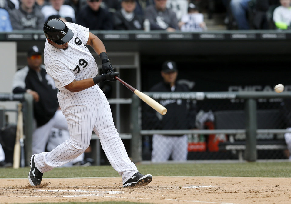 Photo - Chicago White Sox's Jose Abreu hits an RBI single off Minnesota Twins starting pitcher Ricky Nolasco, scoring Adam Eaton, during the third inning of an Opening Day baseball game Monday, March 31, 2014, in Chicago. (AP Photo/Charles Rex Arbogast)
