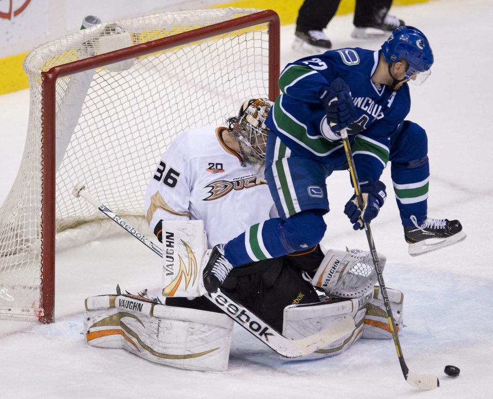 Photo - Vancouver Canucks left wing Daniel Sedin (22) jumps as he tries to get a shot past Anaheim Ducks goalie John Gibson (36) during the first period of NHL action in Vancouver, British Columbia, on Monday, April 7, 2014. (AP Photo/The Canadian Press, Jonathan Hayward)