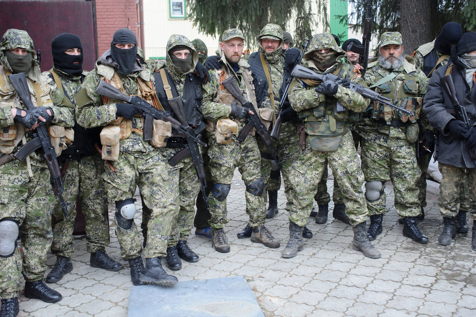 Photo - In this photo taken on Saturday, April  12, 2014, Armed pro-Russian activists pose for a photo after they occupied the police station in the eastern Ukraine town of Slovyansk. Ukraine's interior minister says one security officer has been killed and five others have been wounded in a gunfight with pro-Russian militia. Arsen Avakov said in a Facebook post Sunday the Security Service officer was killed in Slovyansk where a police station was seized by camouflaged armed men. (AP Photo/Maxim Dondyuk, Russian Reporter magazine) MAGAZINES OUT