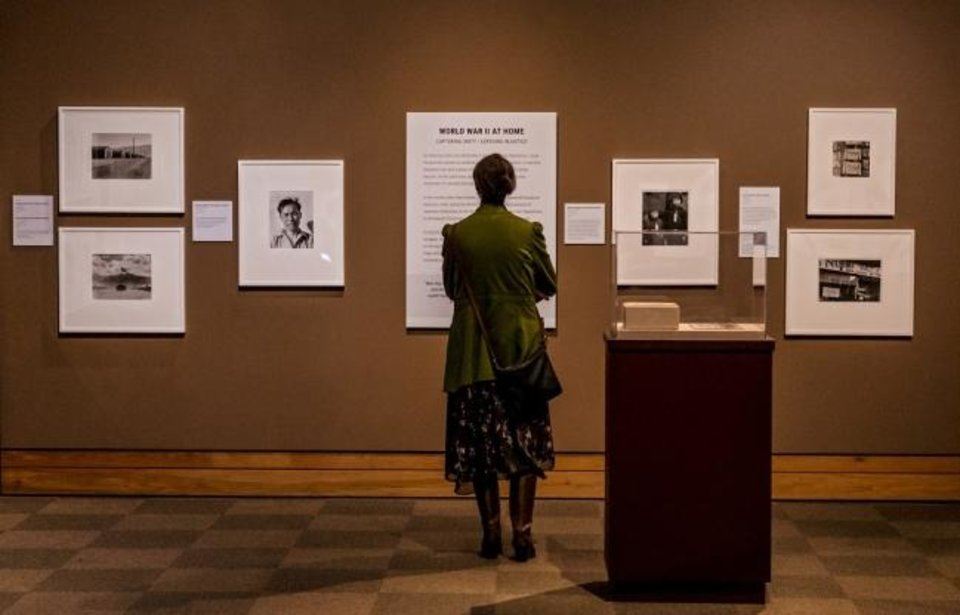 Photo -  A person looks at images on display in the exhibit