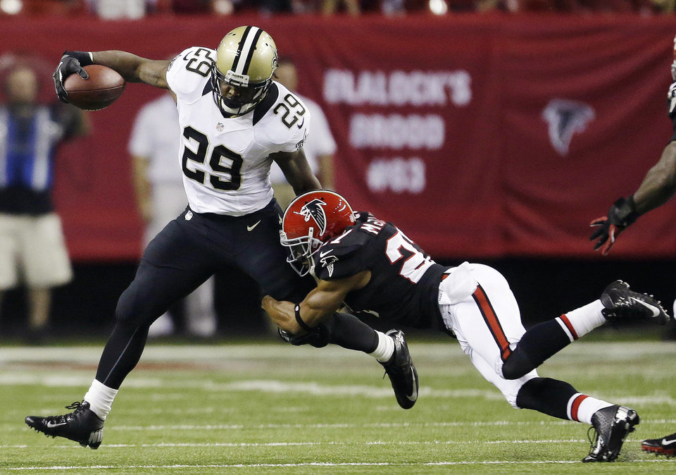 Photo - New Orleans Saints running back Chris Ivory (29) is stopped by Atlanta strong safety William Moore (25) during the first half of an NFL football game, Thursday, Nov. 29, 2012, in Atlanta. (AP Photo/David Goldman)