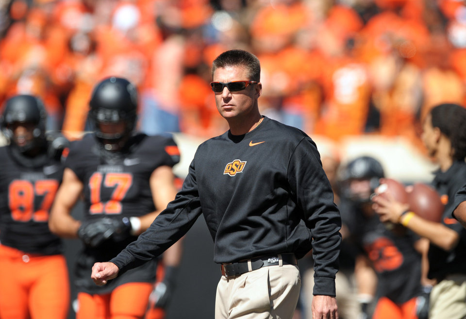 Photo - In this Oct. 5, 2013, photo, Oklahoma State coach Mike Gundy watches his team warm up for an NCAA football game against Kansas State in Stillwater, Okla. Gundy's Cowboys have been among the nation's best with 59 wins since 2008, but they will face Heisman Trophy winner Jameis Winston and the Seminoles after losing about half of last year's letterwinners. (AP Photo/Brody Schmidt)