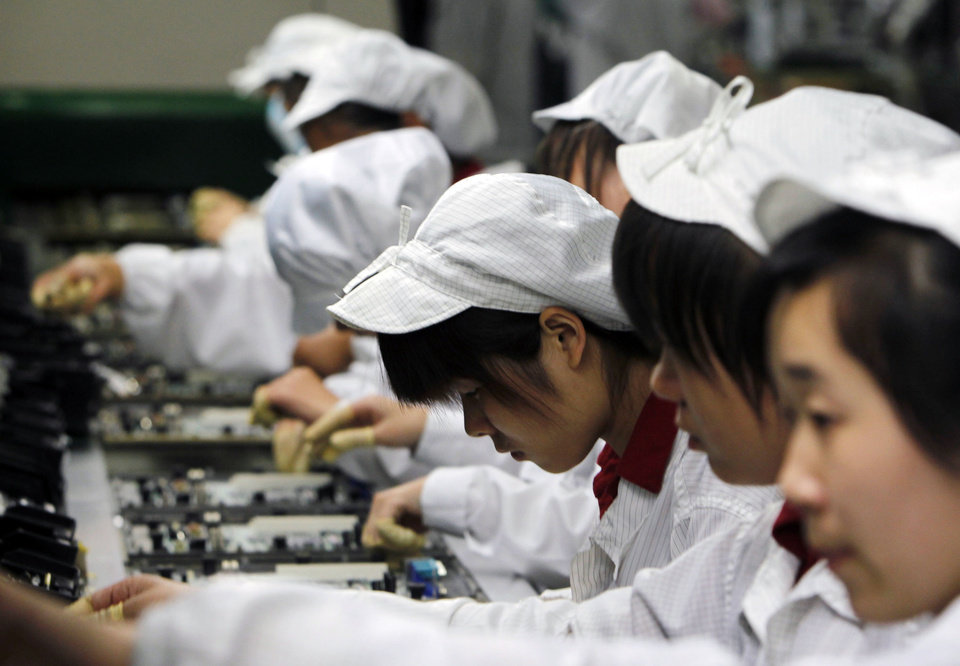 Photo -   FILE-In this Wednesday, May 26, 2010, file photo, staff members work on the production line at the Foxconn complex in Shenzhen, China. Foxconn, the company that makes Apple's iPhones suspended production at a factory in China on Monday, Sept. 24, 2012, after a brawl by as many as 2,000 employees at a dormitory injured 40 people. The fight, the cause of which was under investigation, erupted Sunday night at a privately managed dormitory near a Foxconn Technology Group factory in the northern city of Taiyuan, the company and Chinese police said.(AP Photo/Kin Cheung, File)
