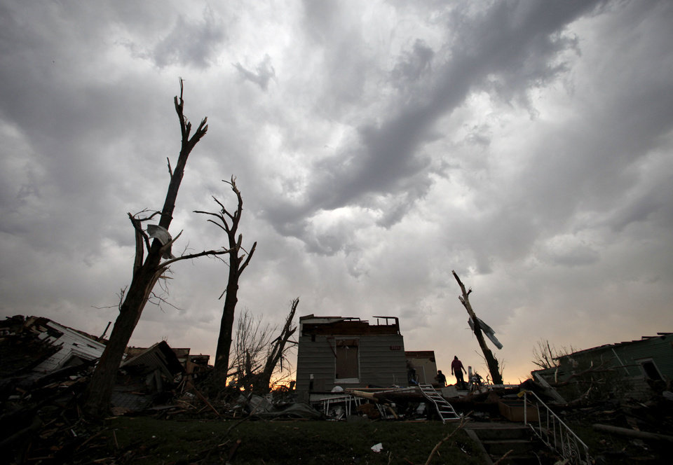 Photo - Residents salvage items from their home which was severely damaged by a tornado in Joplin, Mo., as a severe storm passes overhead Monday, May 23, 2011. A large tornado moved through much of the city Sunday, damaging a hospital, hundreds of homes and businesses and killing at least 89 people. (AP Photo/Charlie Riedel) ORG XMIT: MOCR203