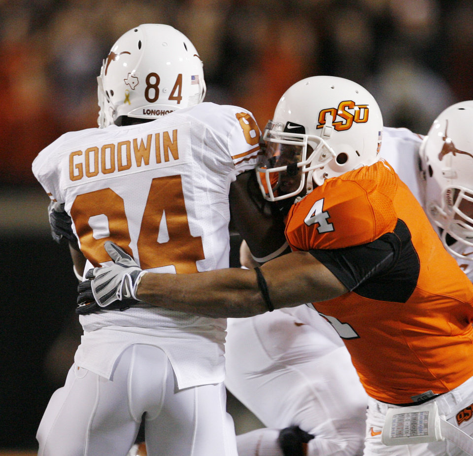 Photo - OSU's Patrick Levine hits Marquise Goodwin (84) of Texas during the college football game between the Oklahoma State University Cowboys (OSU) and the University of Texas Longhorns (UT) at Boone Pickens Stadium in Stillwater, Okla., Saturday, Oct. 31, 2009. Photo by Nate Billings, The Oklahoman