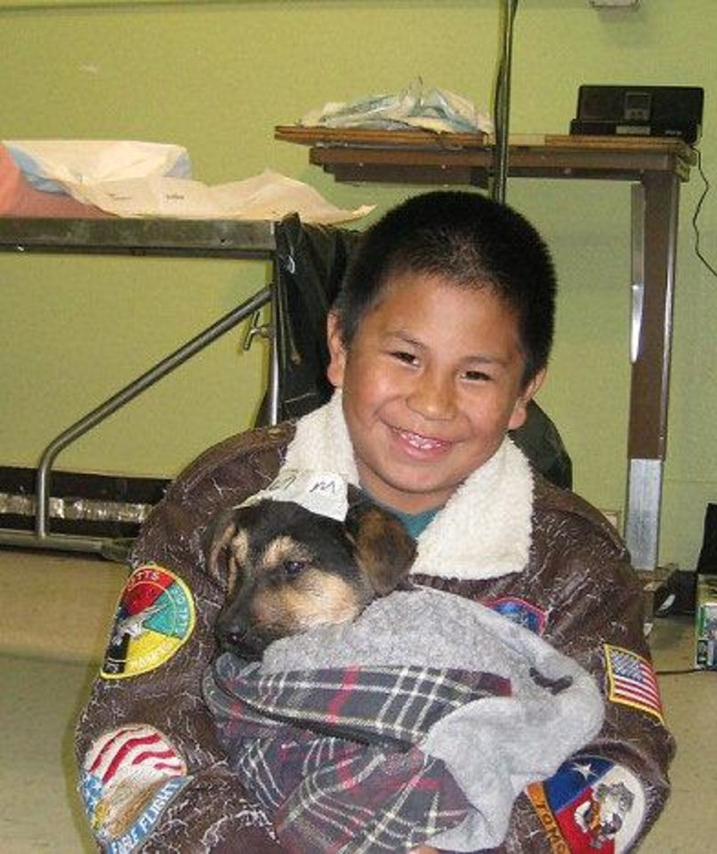 Photo - Above: A boy holds his dog after its neuter  procedure.
