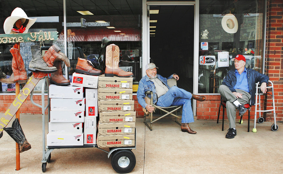 Photo - Dale Scott, left, and Howard Zwirtz sit in front of Scott's dry goods store on Main Street in Hinton and discuss the court decision involving the Hinton Economic Development Authority. PHOTO BY JIM BECKEL, THE OKLAHOMAN