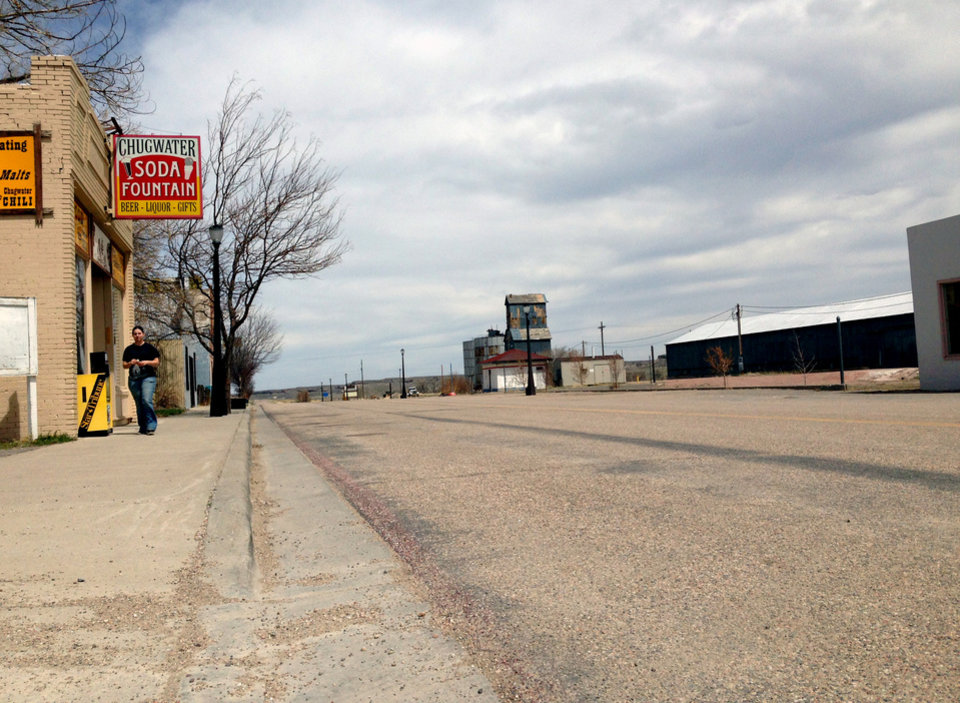 This April 29,2013 photo shows an unidentified woman strolls down an otherwise empty street in Chugwater, Wyo. The 200 or so residents of Chugwater have had nowhere to get gas since a sport utility vehicle crashed into and burned down the Horton\'s Corner convenience store on Dec. 30,2012, which was the town\'s only gas station. Since then, people have had to drive at least 48 miles round-trip to fill up in a neighboring town. (AP Photo/Mead Gruver)