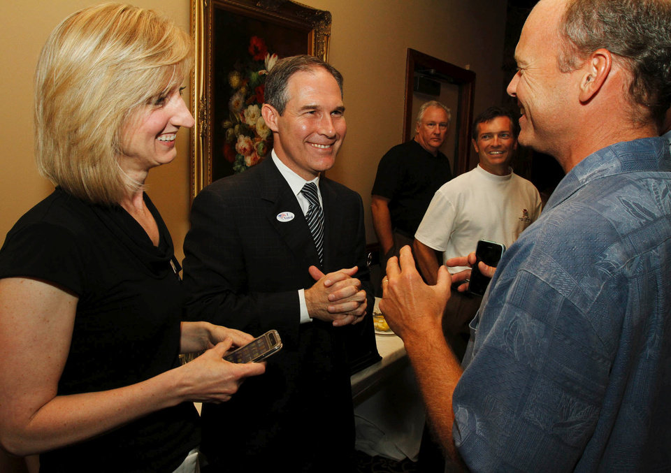 Photo - Republican candidate for Attorney General Scott Pruitt (middle) jokes with his campaign consultants Laurie Spiez and Terry Allen during his watch party at the Cedar Ridge Country Club in Tulsa, Okla., on July 27,2010. JAMES GIBBARD/Tulsa World