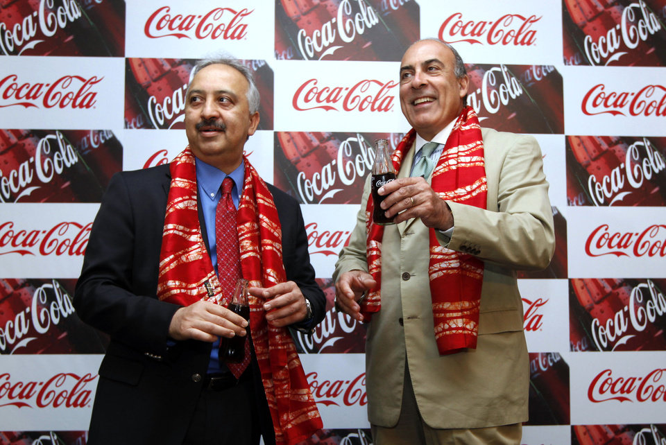 Photo - FILE - In this June 26, 2012 file photo, Chairman and CEO of The Coca-Cola Co., Muhtar Kent, right, and President and CEO of Coca Cola India and South West Asia Atul Singh pose for photos holding bottles of Coca-Cola before the start of a meeting in New Delhi, India. An increasing thirst for Coca-Cola products in China, India and the Middle East helped boost the company's international sales by 3 percent in the second quarter while volume remained flat in North America. (AP Photo/Manish Swarup, File)