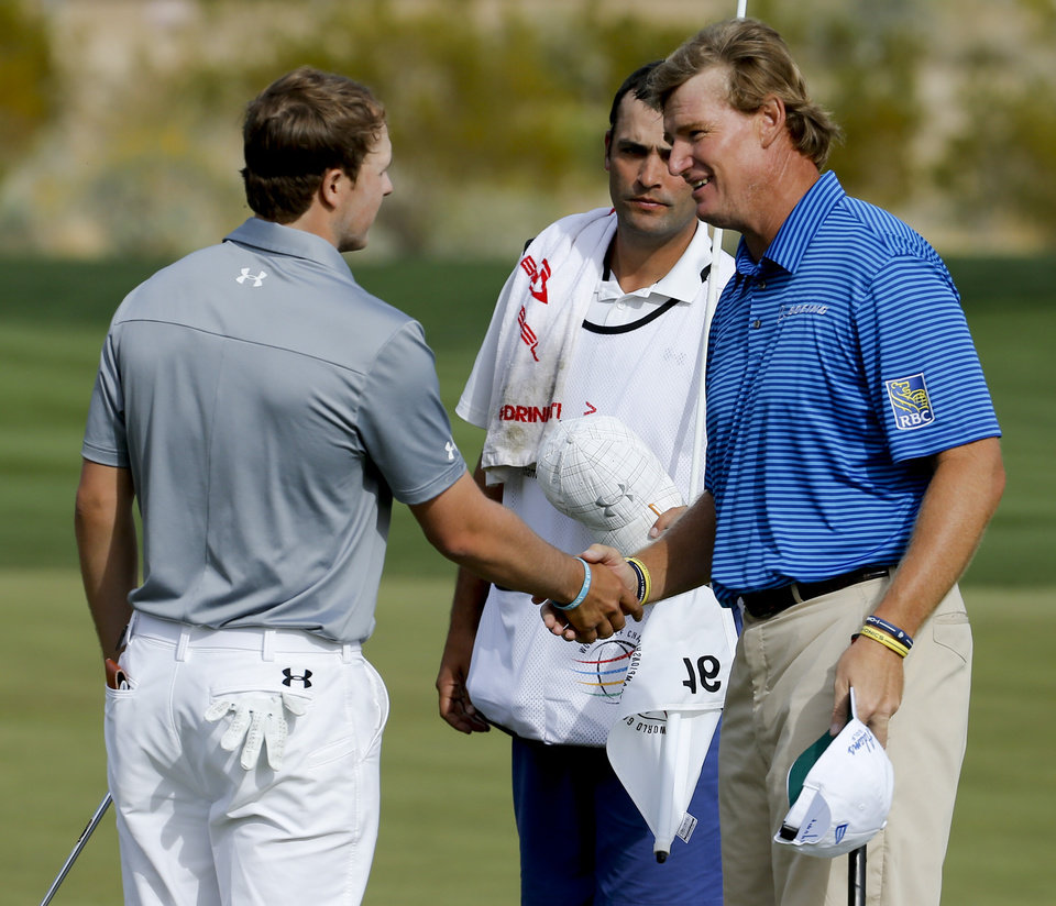 Photo - Ernie Els, right, of South Africa, shakes hands with Jordan Spieth after winning their match on the 17th hole during the fourth round of the Match Play Championship golf tournament on Saturday, Feb. 22, 2014, in Marana, Ariz. (AP Photo/Matt York)