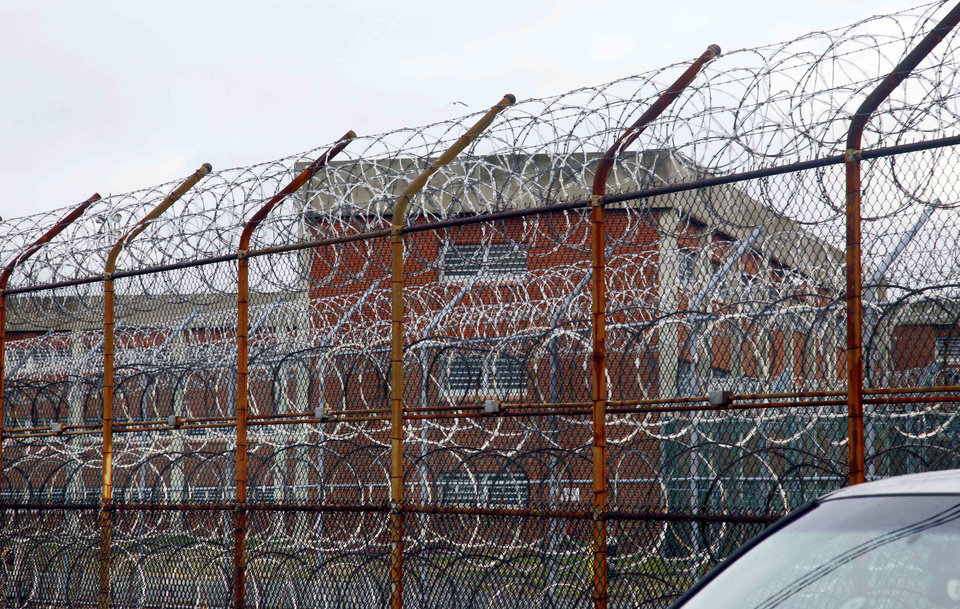 Photo - FILE - In this March 16, 2011 file photo, inmate housing on New York's Rikers Island correctional facility can be seen on the other side of a fence topped with razor wire. The Independent Budget Office found it cost $167,731 in 2012 to house 12,287 daily New York City inmates, which is about $460-per-inmate-per-day. (AP Photo/Bebeto Matthews, File)