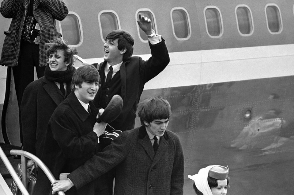 "Photo - FILE - This Feb. 7, 1964 file photo shows The Beatles, from left, Ringo Starr, John Lennon, Paul McCartney and George Harrison arriving in New York at John F. Kennedy airport. Sunday marks the 50th anniversary of The Beatles' performance on ""Ed Sullivan,"" their first appearance in America. Nielsen says 45 percent of all TV sets in use at the time were tuned into the broadcast, with fans and the uninitiated alike gathered shoulder to shoulder in their living rooms. The Beatles landed on a trigger point when they hit America. It was a pop culture sonic boom spurred by talent, timing and luck that's still rattling the windows. (AP Photo, File)"