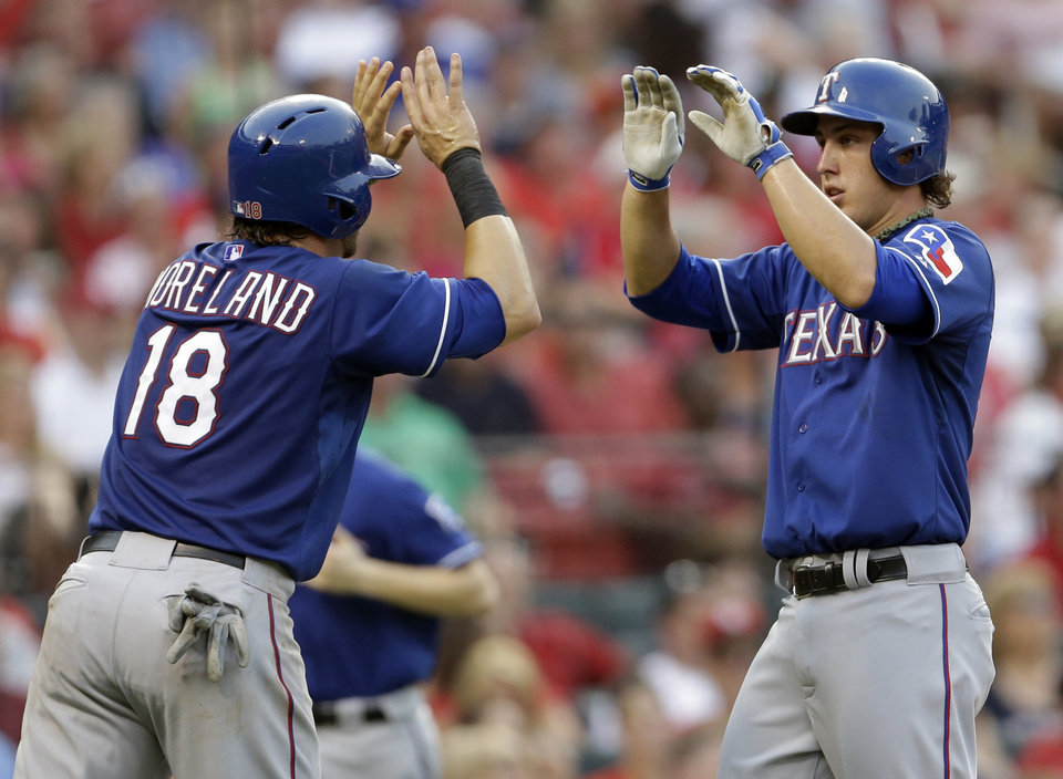 Photo - Texas Rangers' Mitch Moreland, left, and Derek Holland celebrate after scoring on a single by Elvis Andrus against the St. Louis Cardinals during the second inning of an interleague baseball game on Friday, June 21, 2013, in St. Louis. (AP Photo/Jeff Roberson)