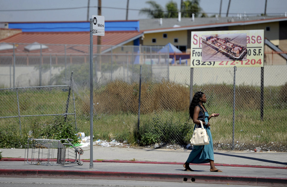 Photo -   In this Tuesday April 17,2012 photo a woman walks past an empty lot on Vermont Ave. between 85th St. and Manchester Ave. in South Central Los Angeles. Several large stores once occupied the lot that was looted and set afire during the riots of 1992. Twenty years since the 1992 LA riots residents of the city's largely black and Hispanic South Side complain that the area still is plagued by too few jobs, too few grocery stores and a lack of redevelopment that would bring more life to the area. (AP Photo/Chris Pizzello)