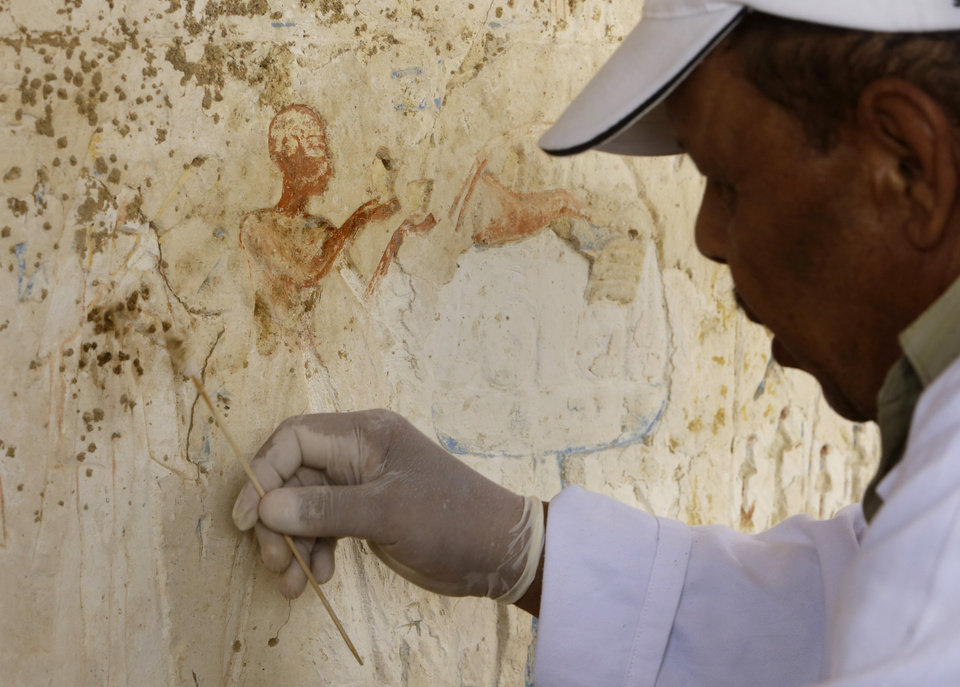 """Photo - An Egyptian conservator works at a newly-discovered tomb dating back to around 1100 B.C. at the Saqqara archaeological site, 30 kilometers (19 miles) south of Cairo, Egypt, Thursday, May 8, 2014. Antiquities Minister Mohamed Ibrahim said Thursday that the tomb belongs to a guard of the army archives and royal messenger to foreign countries. Ibrahim says the Cairo University Faculty of Archaeology's discovery at Saqqara adds """"a chapter to our knowledge about the history of Saqqara."""" Saqqara was the necropolis for the ancient Egyptian city of Memphis and site of the oldest known pyramid in Egypt.(AP Photo/Amr Nabil)"""