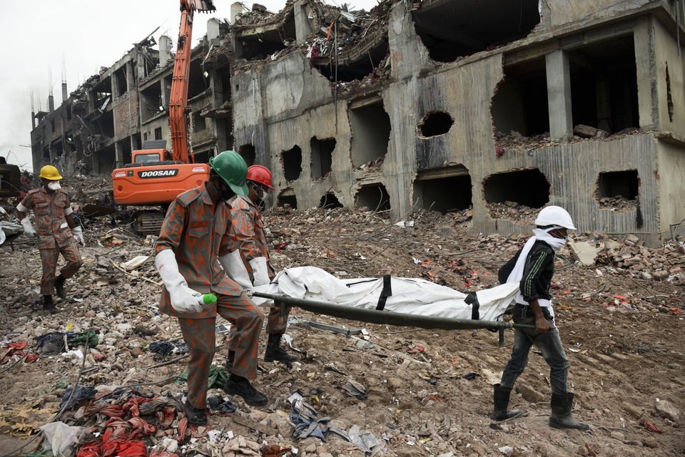 Photo - Rescuers carry a body retrieved from the rubble of the eight-story Rana Plaza building that collapsed in Savar, near Dhaka, Thursday, May 9, 2013. The death toll from the collapse of the garment factory building passed 900 on Thursday even as a fire in an 11-story garment factory Wednesday night in Dhaka killed eight people, including a ruling-party politician and a top official in the country's powerful clothing manufacturers' trade group. (AP Photo/Ismail Ferdous)