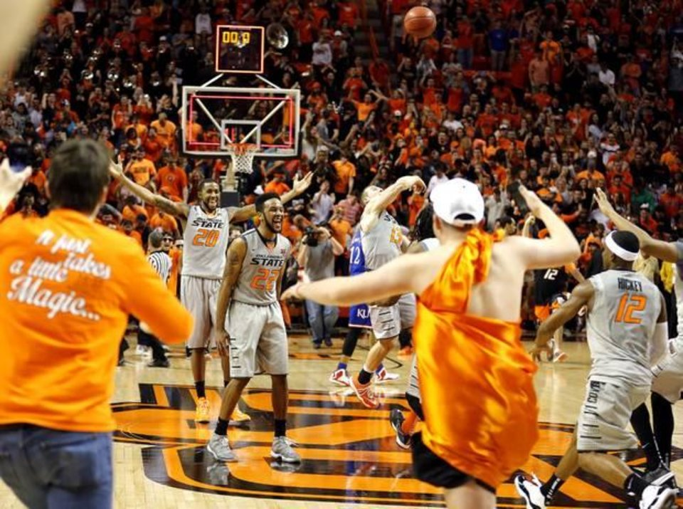 Photo - Oklahoma State's Michael Cobbins (20), Jeff Newberry (22) and Phil Forte III (13) celebrate as fans rush the court following the men's college basketball game between Oklahoma State University and the University of Kansas at Gallagher-Iba Arena in Stillwater, Okla., Saturday, Feb. 7, 2015. OSU won 67-62. Photo by Sarah Phipps, The Oklahoman
