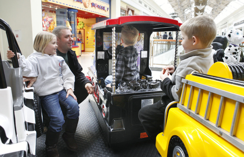 Photo - Six-year-old Meghan Hailey and her dad Randy, as well as six-year-old Nicholas Reed (right) watch as four-year-old Gavin Hailey rides a ride at Penn Square Mall in Oklahoma City, OK, Thursday, Feb. 3, 2011. By Paul Hellstern, The Oklahoman