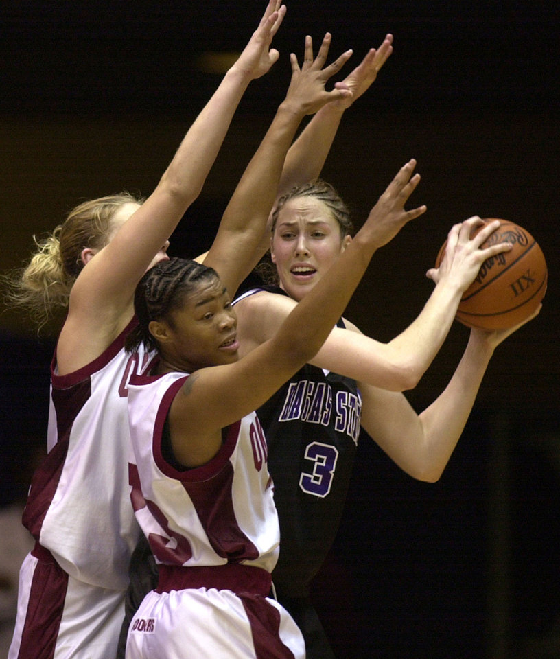 OU: University of Oklahoma women's college basketball against Kansas State University during the semi final round of Women's Big 12 tournament in Municipal Auditorium, Kansas City, Missouri, Thursday, March 7, 2002.  Nicole Ohlde of Kansas State looks for an open teammate while surrounded by Rosalind Ross, middle, and Caton Hill.  Staff photo by Bryan Terry