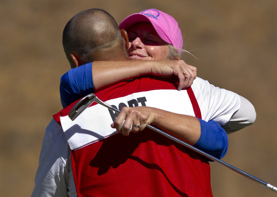 Photo - In this image provided by the USGA, Ellen Port embraces her caddie, Carlos Cortez, as they celebrate her 3 and 2 victory in the final round of match play against Susan Cohn at the USGA Senior Women's Amateur Championship golf tournament at CordeValle Golf Club in San Martin, Calif, on Thursday, Sept, 26 2013. Port won 3 and 2. (AP Photo/USGA, Steve Gibbons)
