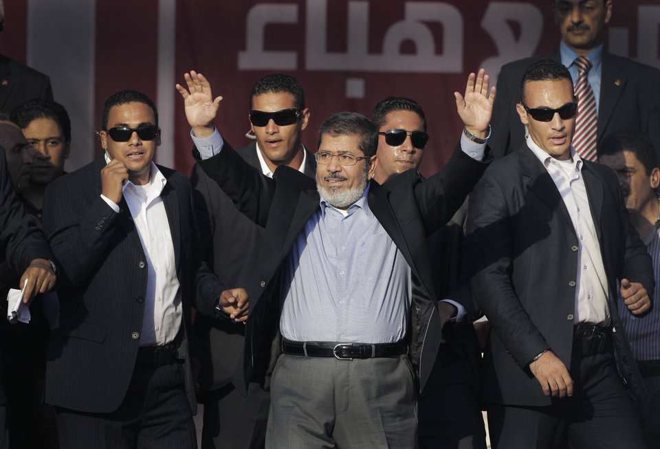 Photo -   FILE - In this Friday, June 29, 2012 file photo, Egypt's new President-elect Mohammed Morsi waves to supporters at Tahrir Square, the focal point of Egyptian uprising, in Cairo, Egypt. Standing before tens of thousands of adoring supporters in Tahrir Square, Morsi opened his jacket to show he is not wearing a bullet-proof vest. The message is clear: He has nothing to fear because he sees himself as the legitimate representative of Egypt's uprising. His speeches reveal a populist bent, making generous promises that many are skeptical he can keep. And though he began as an awkward and uninspiring speaker, he appears to be striving to reinvent his decidedly uncharismatic public persona. (AP Photo/Amr Nabil, File)