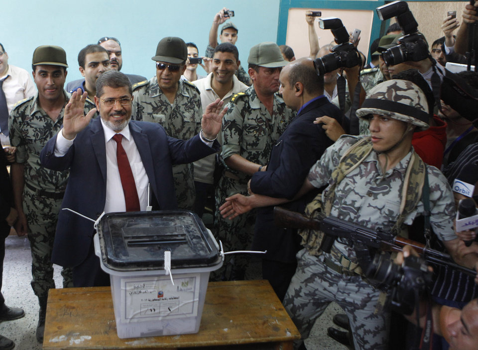 Photo - FILE - In this Saturday, June 16, 2012 file photo, Egyptian presidential candidate Mohammed Morsi waves after he casts his vote at a polling station in Zagazig, 63 miles (100 kilometers) northeast of Cairo, Egypt. Egypt's newly announced criminal investigation against Mohammed Morsi is likely just the start of wider legal moves against the ousted president and his Muslim Brotherhood _ ominous prospects for a country seething with violent divisions. During three weeks of secret detention, military intelligence has extensively questioned Morsi on the inner workings of his presidency and of the Brotherhood, seeking to prove he committed crimes including handing state secrets to the Islamist group. Military officials tell The Associated Press the interrogations could land Morsi in court in lead to a renewed ban for the Brotherhood.(AP Photo/Amr Nabil, File)