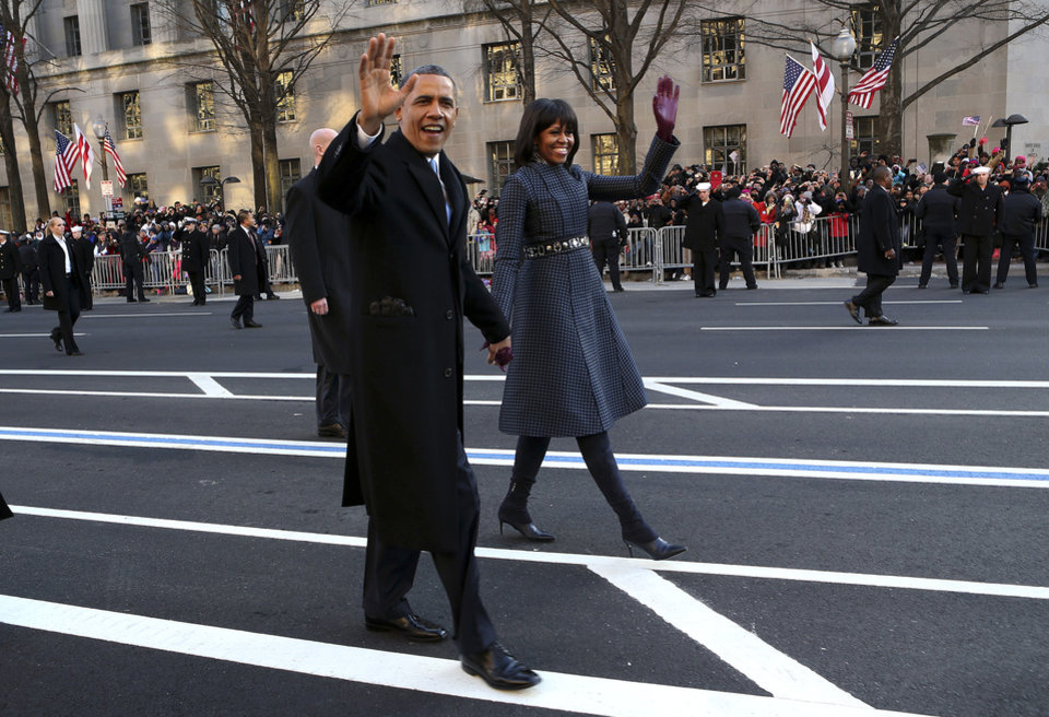 Photo - President Barack Obama and first lady Michelle Obama wave as they walk down Pennsylvania Avenue in Washington, Monday, Jan. 21, 2013, during the Inaugural Parade after his ceremonial swearing-in on Capitol Hill during the 57th Presidential Inauguration. (AP Photo/The New York Times, Doug Mills, Pool) ORG XMIT: NYNYT308
