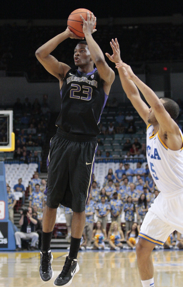 Washington guard C.J. Wilcox (23) shoots the ball as UCLA's Jerime Anderson defends during the first half of an NCAA college basketball game, Saturday, March 3, 2012, in Los Angeles. (AP Photo/Jason Redmond)