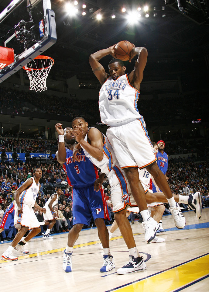 Photo - Oklahoma City's Desmond Mason (34) grabs a rebound next to Russell Westbrook (0) and Detroit's Rodney Stuckey (3) during the NBA basketball game between the Detroit Pistons and the Oklahoma City Thunder at the Ford Center in Oklahoma City, Friday, January 16, 2009. Oklahoma City won, 89-79. By Nate Billings, The Oklahoman ORG XMIT: KOD