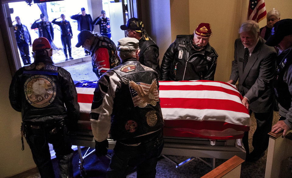 Photo - Members of the Patriot Guard Riders salute the casket of homeless Army veteran William Eugene Weeks Jr., 64, as it is carried out of the chapel after the funeral of Weeks at Chapel Hill Funeral Home in Oklahoma City, Okla. on Wednesday, Oct. 24, 2018.   Photo by Chris Landsberger, The Oklahoman