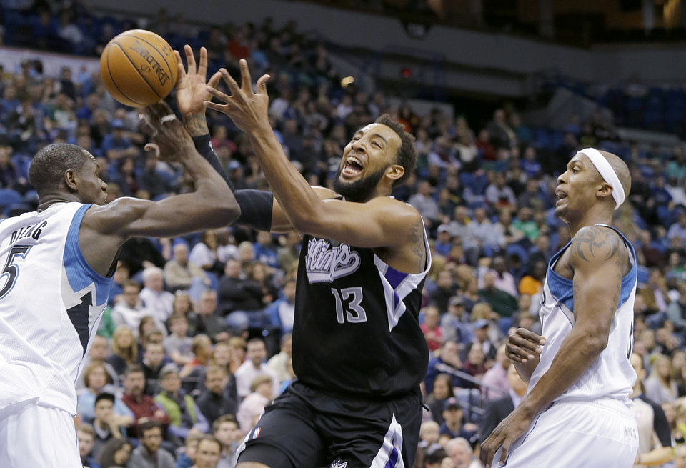 Photo - Minnesota Timberwolves center Gorgui Dieng, left, strips the ball from Sacramento Kings forward Derrick Williams (13) as Williams drives to the basket between Dieng and Timberwolves forward Dante Cunningham, right,  during the second quarter of an NBA basketball game in Minneapolis, Sunday, March 16, 2014. (AP Photo/Ann Heisenfelt)