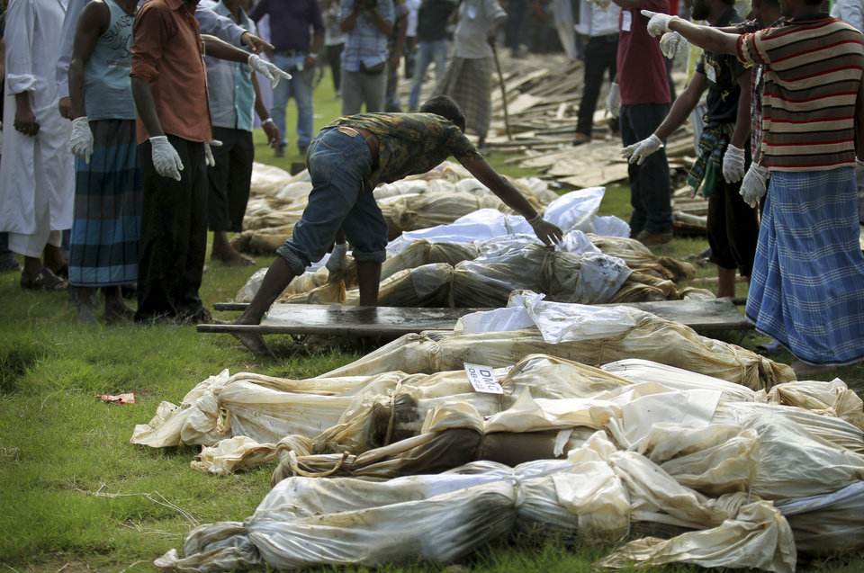 Workers line up unclaimed bodies from the building that collapsed last week in preparation for a mass burial on Wednesday, May 1, 2013, in Dhaka, Bangladesh. Several hundred people attended a mass funeral in a Dhaka suburb for 18 unidentified workers who died in the building housing garment factories that collapsed last week in the country's worst industrial disaster, killing at least 402 people and injuring 2,500.   (AP Photo/Wong Maye-E)