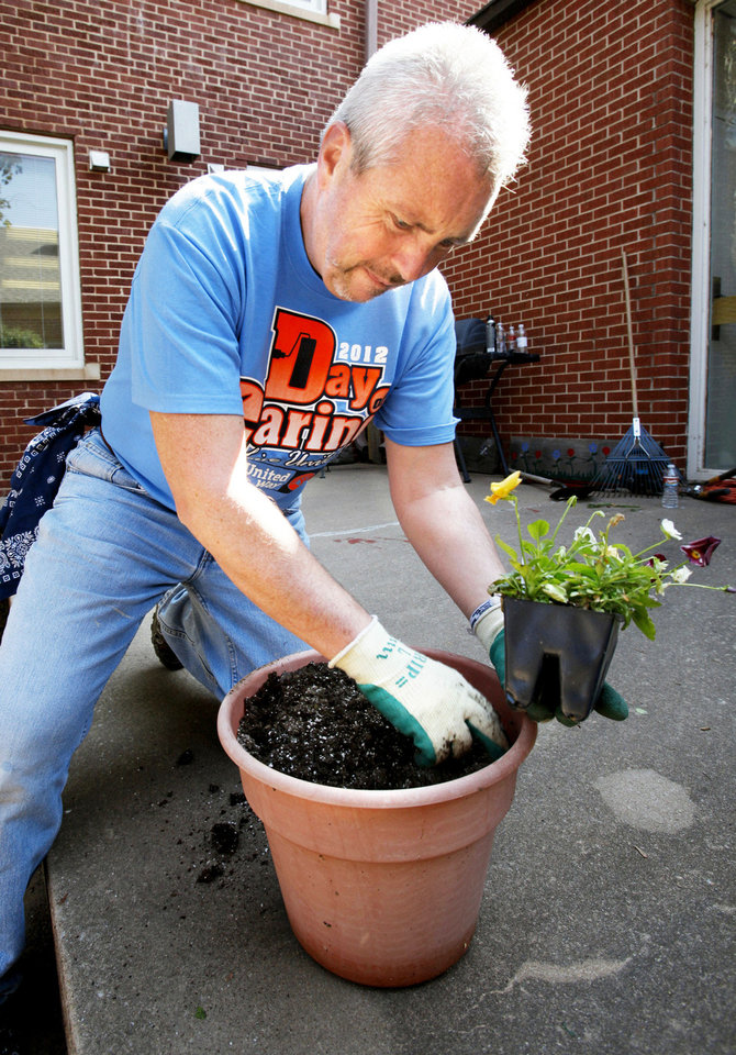 United Way volunteer Bart Byrns, with First American Bank, plants flowers Friday at the Community Services  Building in Norman as part of this year�s Day of Caring event.