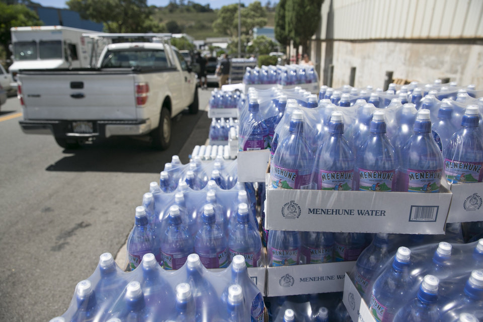 Photo - Cases of water are seen curbside at the Menehune Water Company, Aug. 7, 2014, in Aiea, Hawaii.  Hawaii is bracing for two back to back hurricanes, Iselle and Julio, which are on course to hit the Islands.  Bottles of water are quickly disappearing off shelves in Hawaii causing many people to line up for several hours to purchase water directly from the company.  (AP Photo/Marco Garcia)