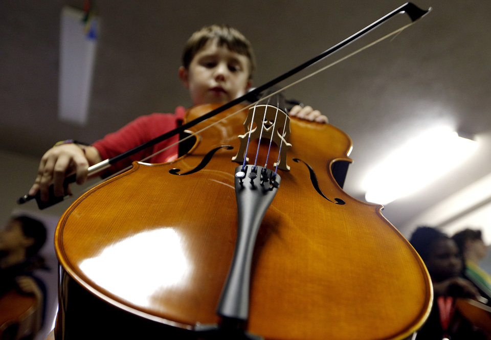 Photo - Elliott Miller plays the cello for the first time during a session of a new after-school music program called  El Sistema Oklahoma. The program, which meets at Trinity Baptst International Church,  1329 NW 23, is a partnership between St. Luke's United Methodist Church, Oklahoma City University and the Foundation for Oklahoma City Public Schools.  SARAH PHIPPS - SARAH PHIPPS