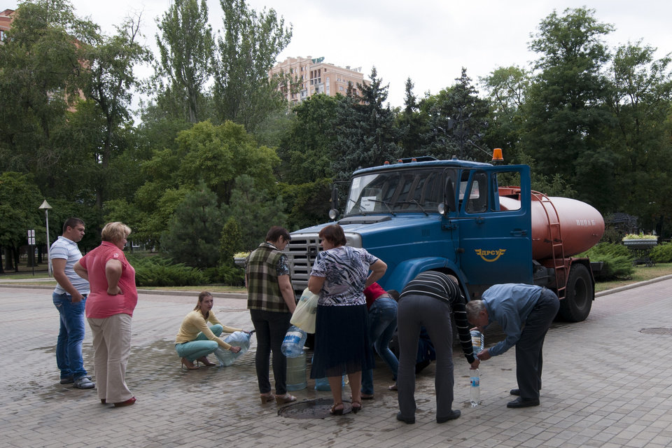 Photo - In this photo taken Tuesday, Aug. 19, 2014 residents line up to collect drinking water in Donetsk, eastern Ukraine. After days of street battles and weeks of shelling, Ukrainian troops made significant gains Wednesday upon rebel-held territory, capturing a large part of the city of Luhansk and encircling Donetsk, the largest rebel-held city, in fighting that left at least 43 dead. (AP Photo/Antoine E.R. Delaunay)